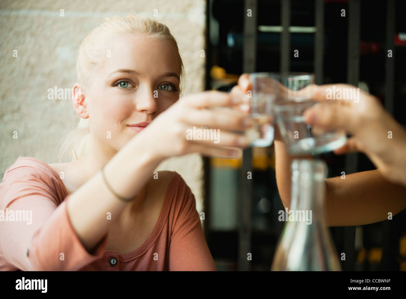 Young blond woman raising glass - Stock Image