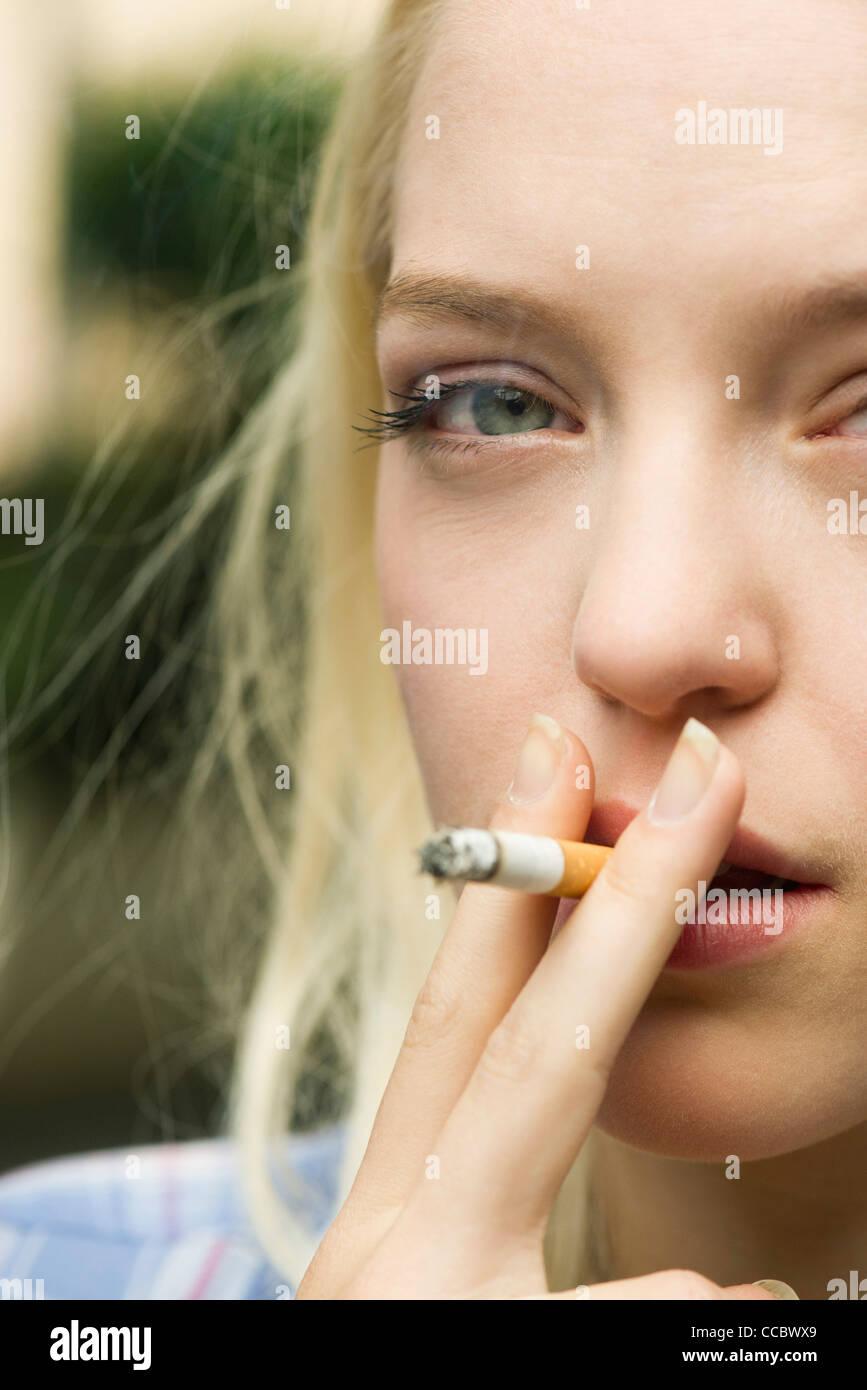 Young woman smoking cigarette - Stock Image