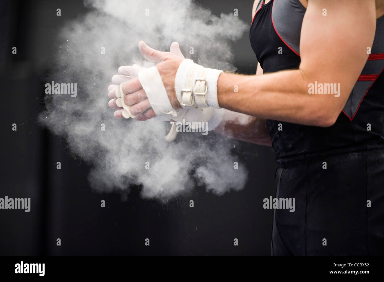 Gymnast applying chalk power to hands in preparation - Stock Image