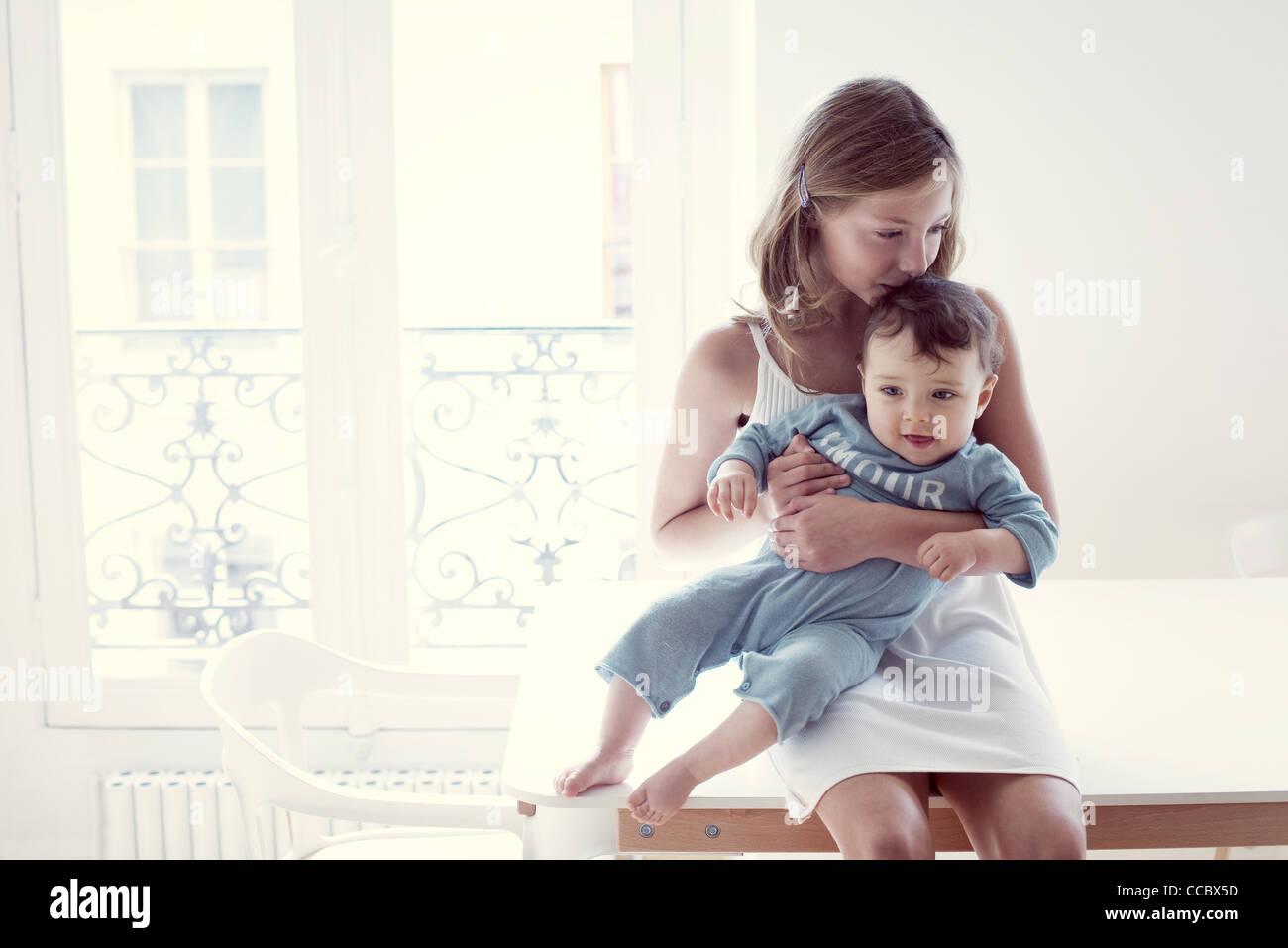 Girl kissing baby sister on lap, portrait - Stock Image