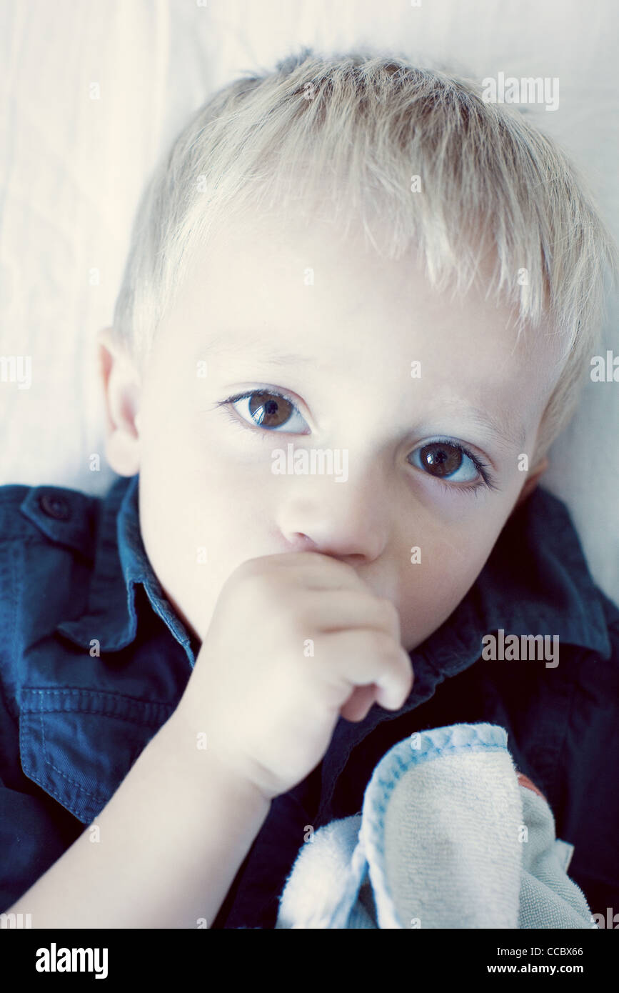 Little boy sucking his thumb, portrait - Stock Image