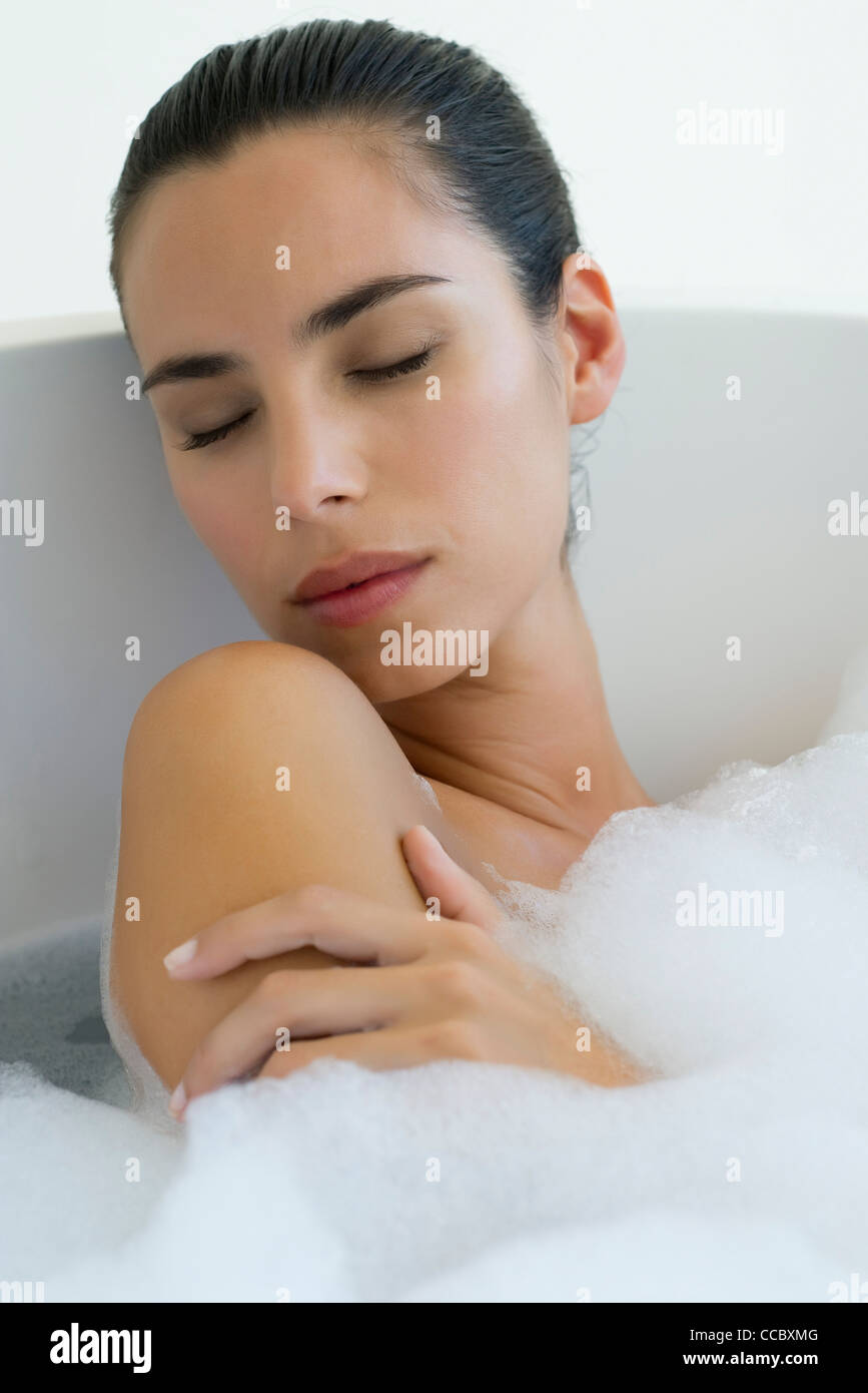 Woman taking bubble bath with eyes closed - Stock Image