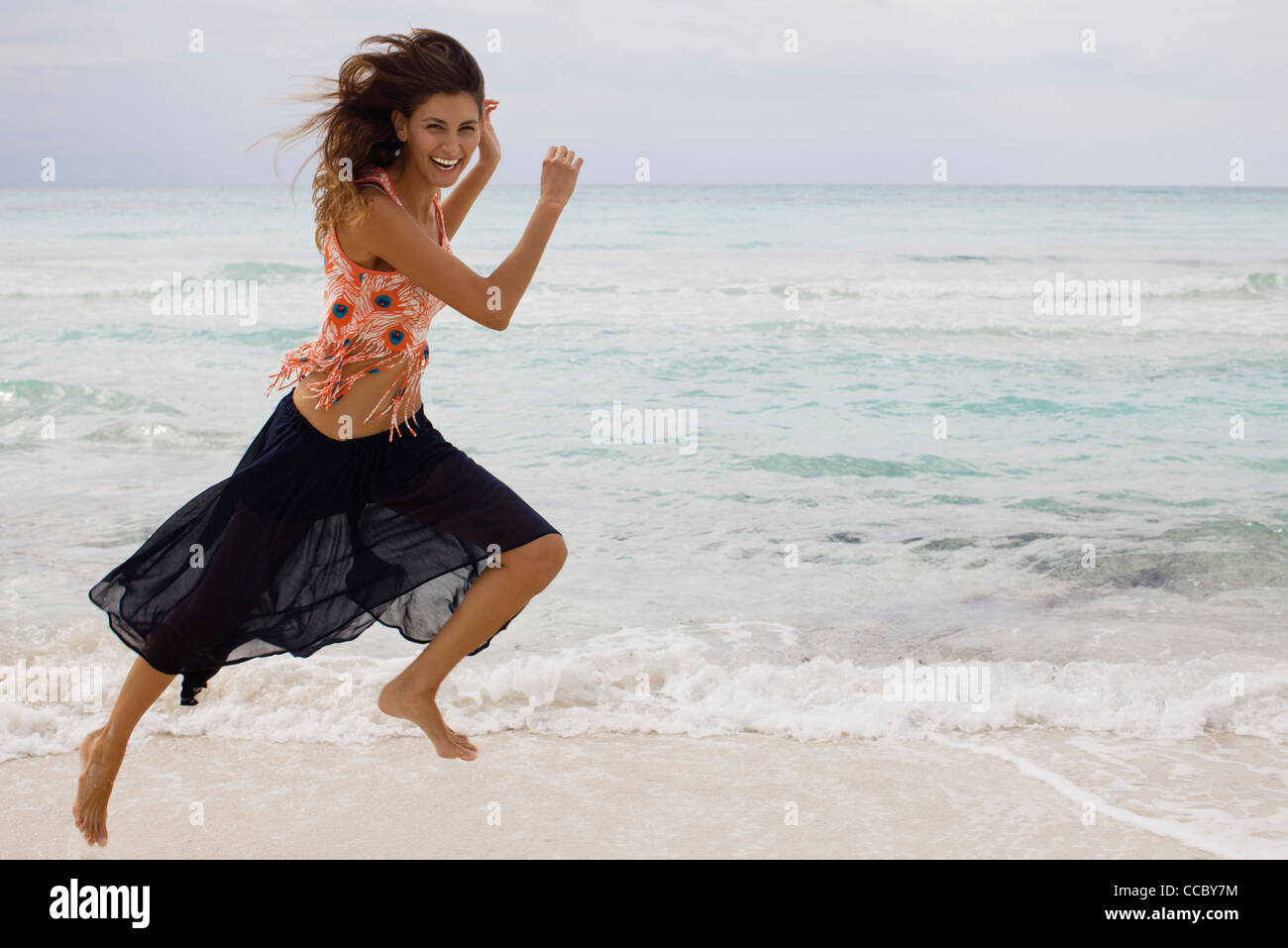 Woman running at the beach - Stock Image