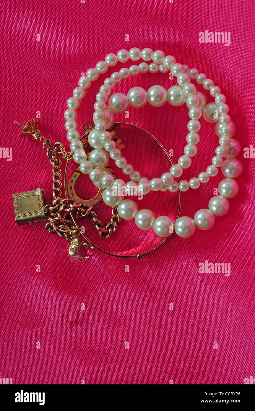 Three artificial pearl bracelets a gold bangle and gold charm bracelet made from a gold watch chain. - Stock Image
