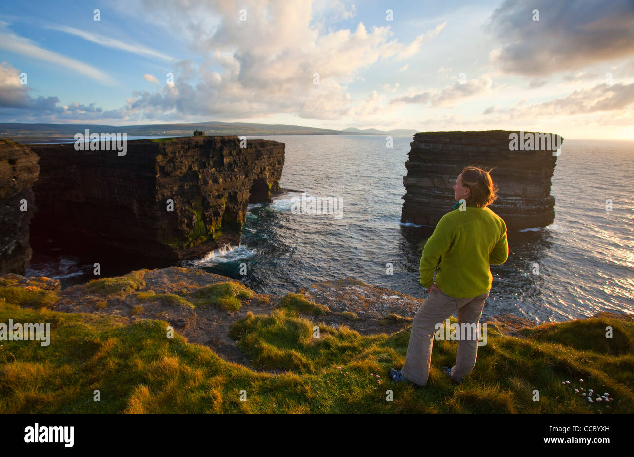 Person admiring Downpatrick Head and Dun Briste seastack, County Mayo, Ireland. - Stock Image