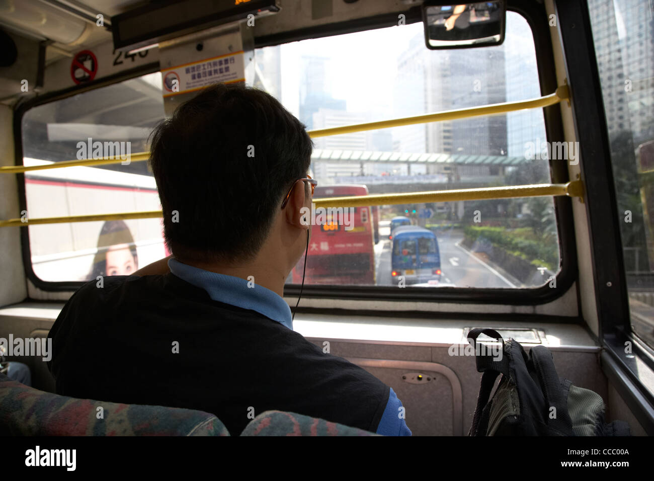 chinese man with earphones and backpack commuting on the front seat of a double deck bus downtown hong kong hksar - Stock Image