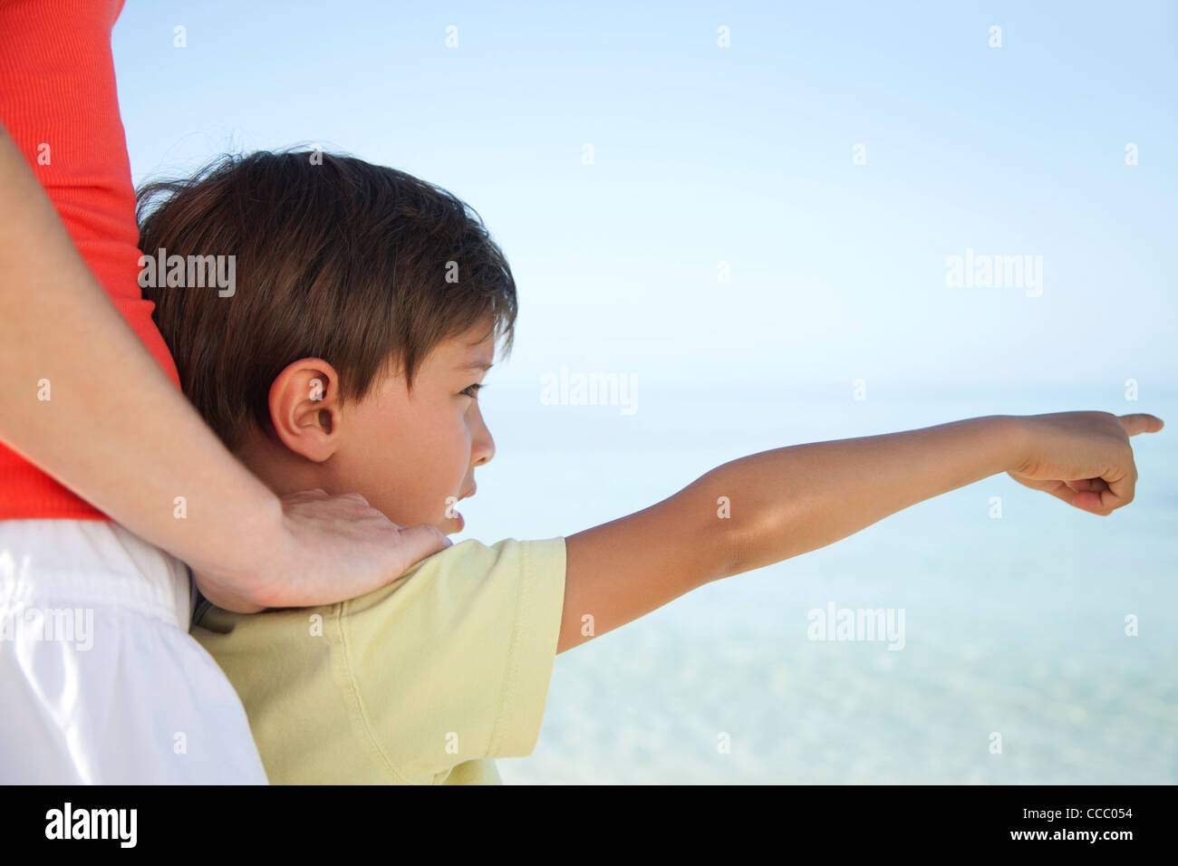 Boy pointing at sea - Stock Image