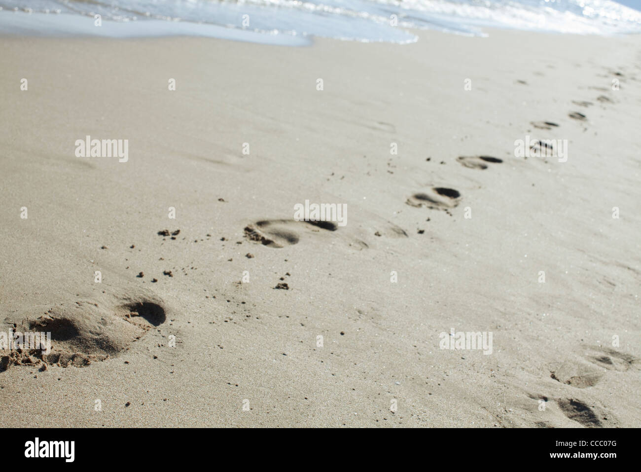 Footprints in sand at the beach - Stock Image