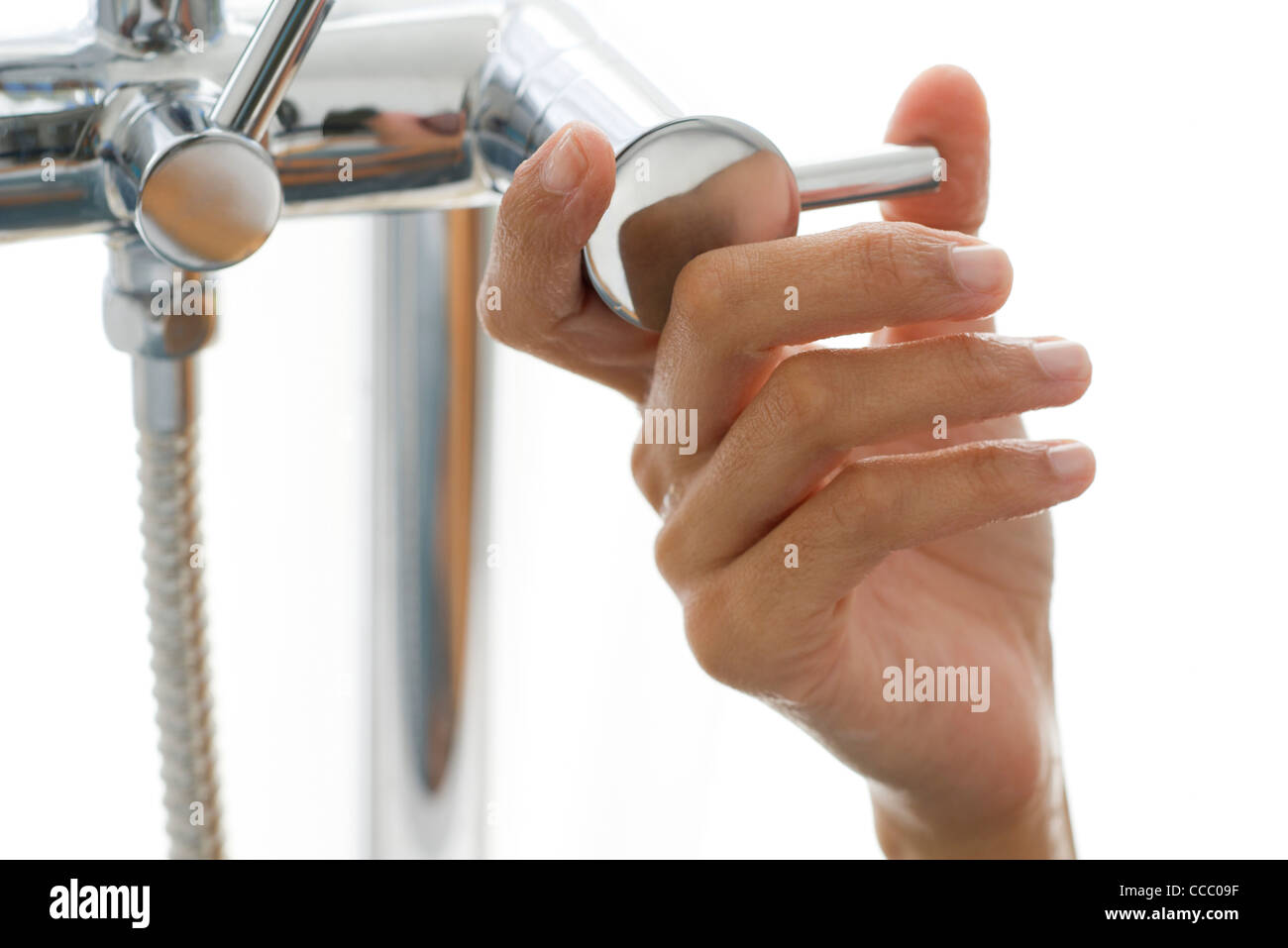 Woman's hand turning faucet - Stock Image