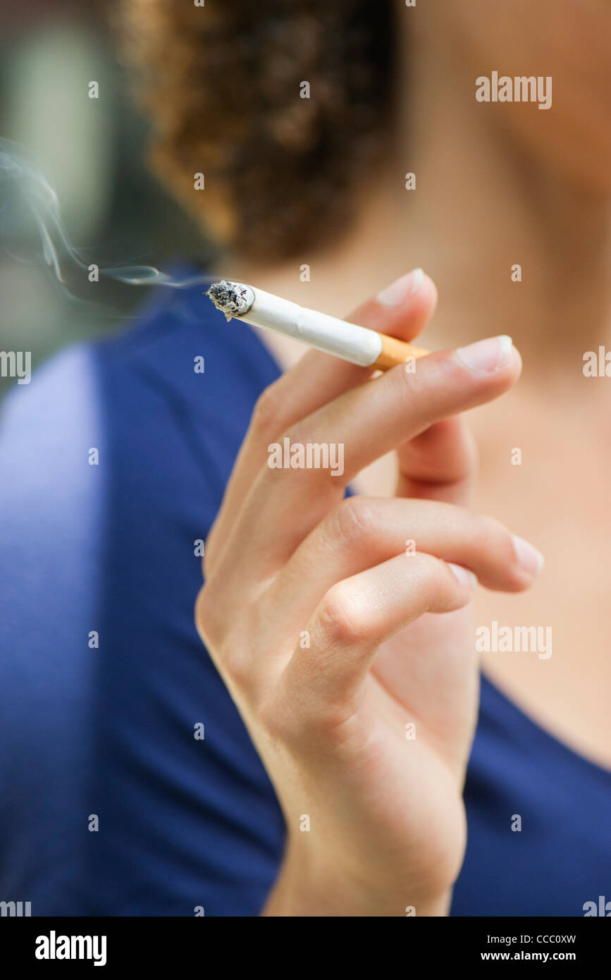 Woman's hand holding lit cigarette - Stock Image