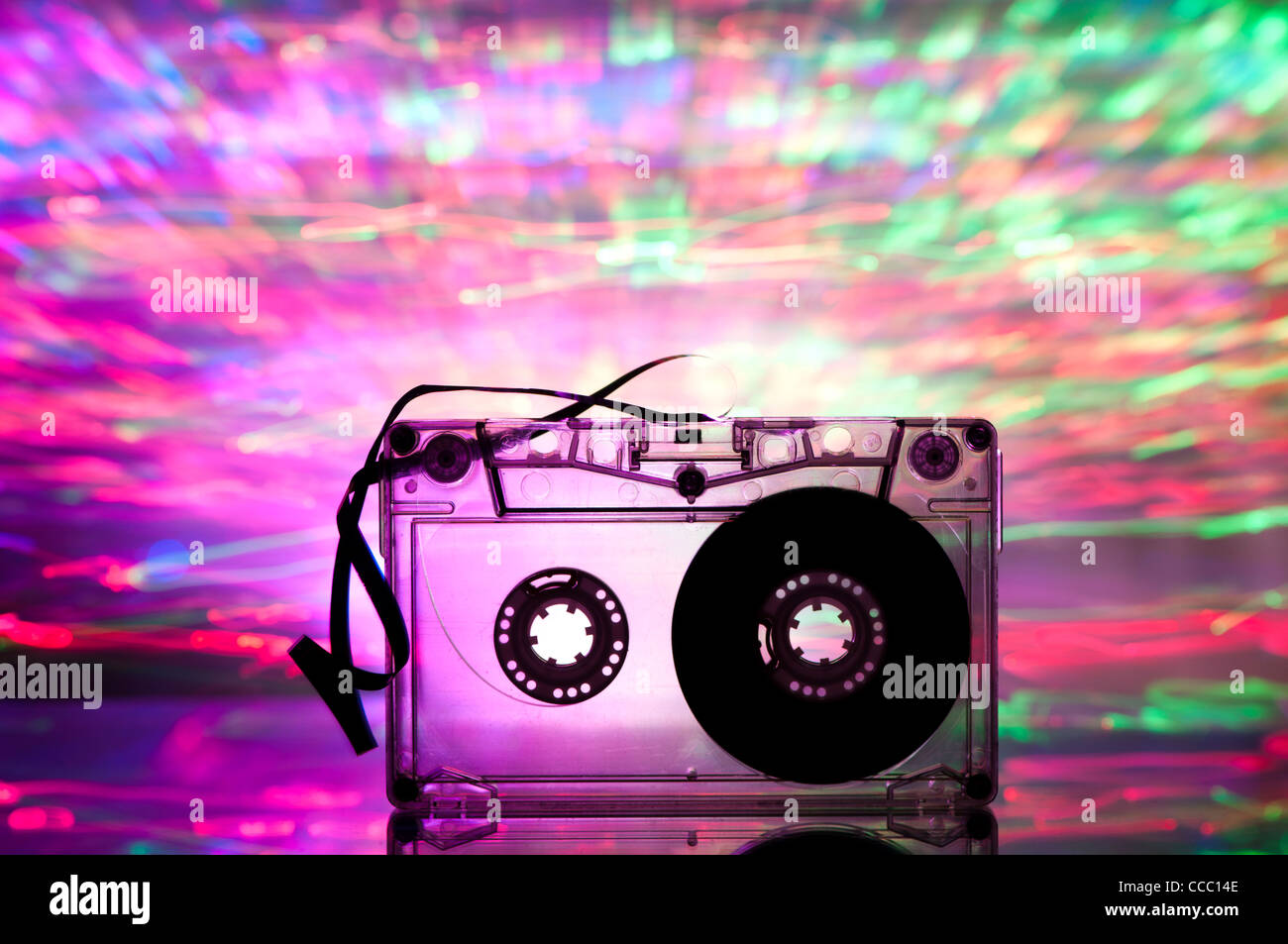 Cassette tape and multicolored pink blue lights on background - Stock Image