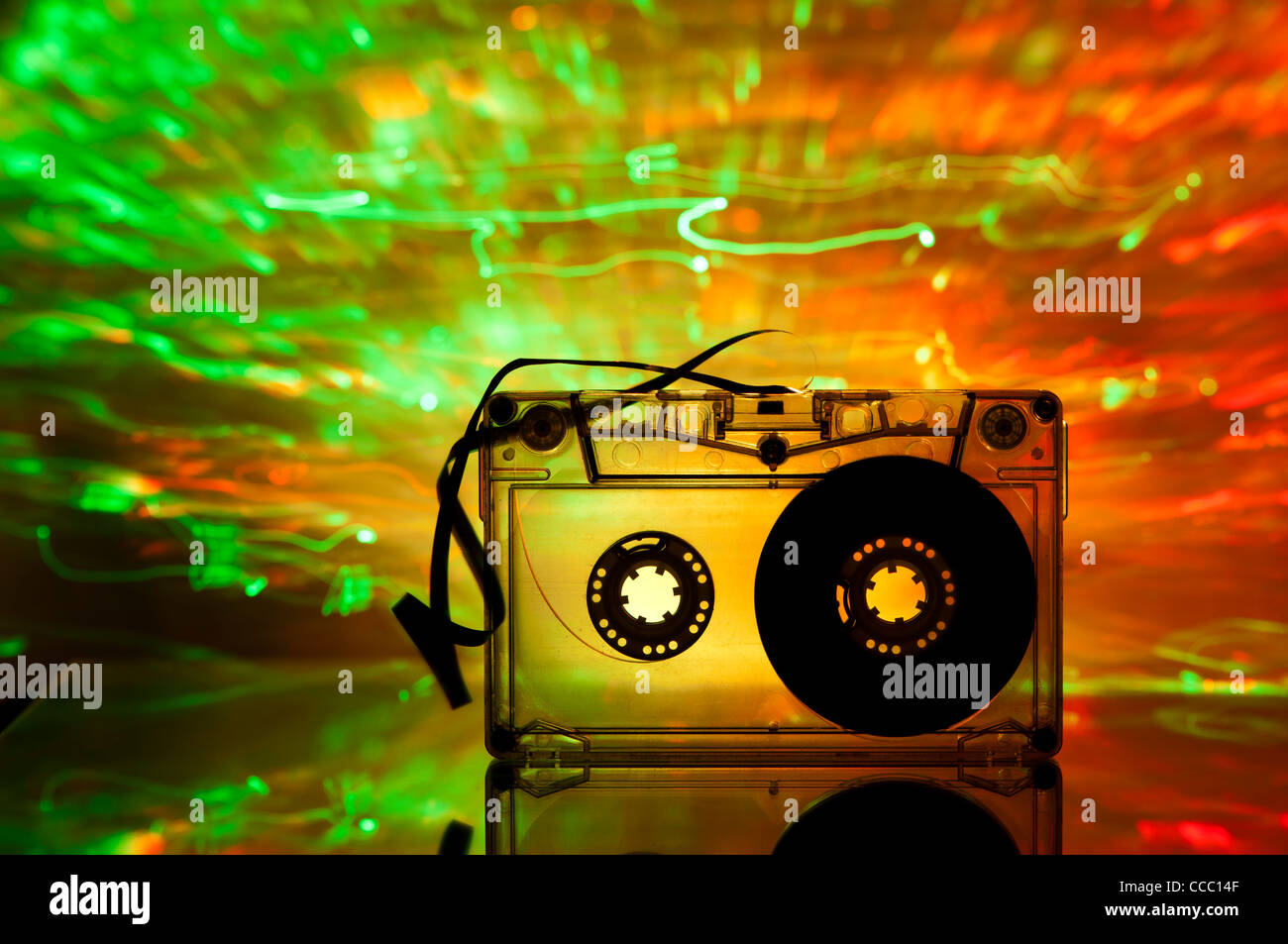 Cassette tape and multicolored yellow green lights on background - Stock Image