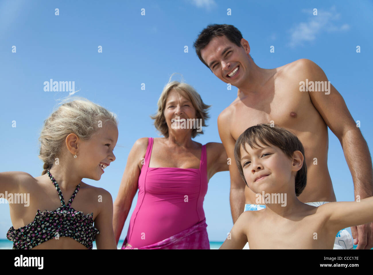 Multi-generation family having fun at the beach - Stock Image