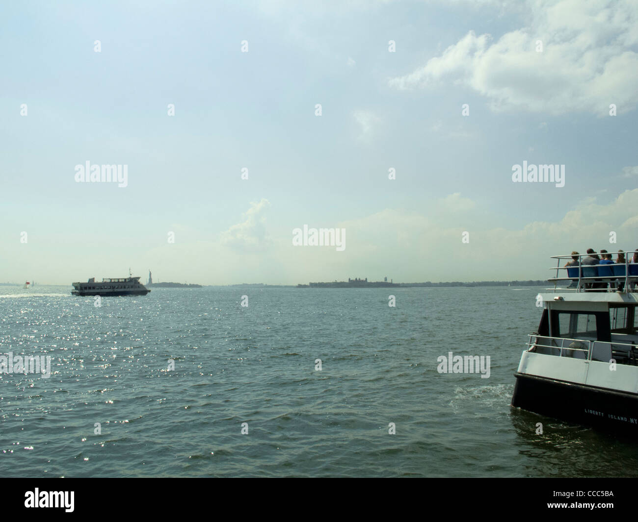 summer ferry ride to governors island, across new york harbor, statue of liberty in back ground. - Stock Image