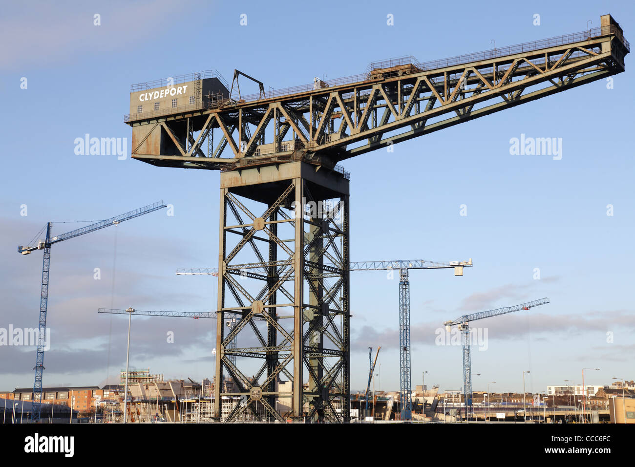 Construction cranes beside the Finnieston Crane in Glasgow, Scotland, UK - Stock Image