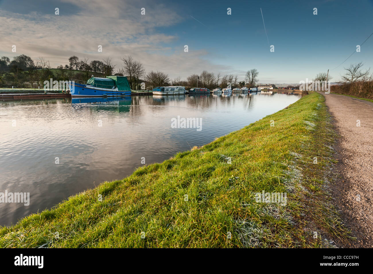 Boats on a canal with a frosty towpath and blue cloudy sky - Stock Image
