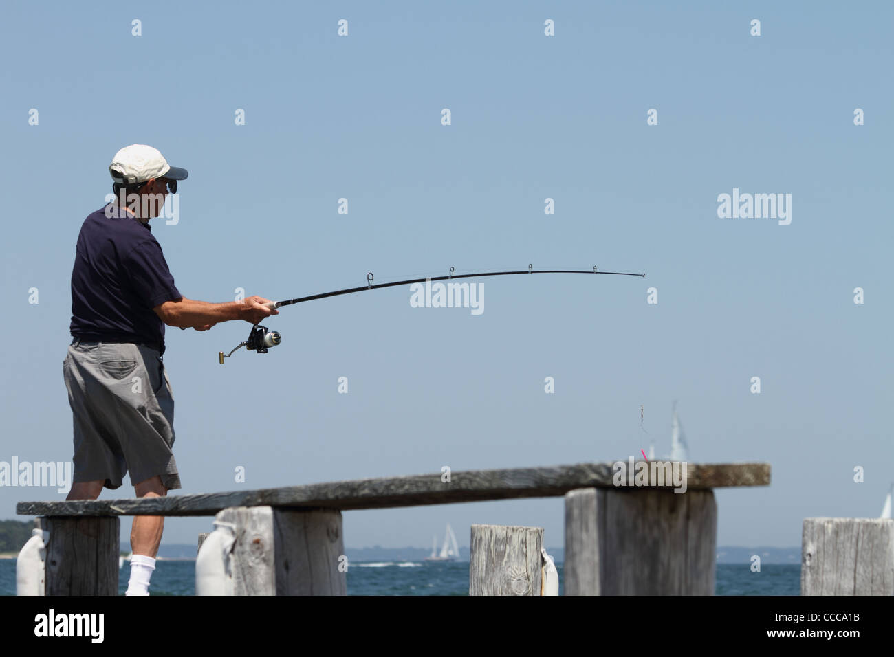 full back view of senior male fishing from pier Stock Photo