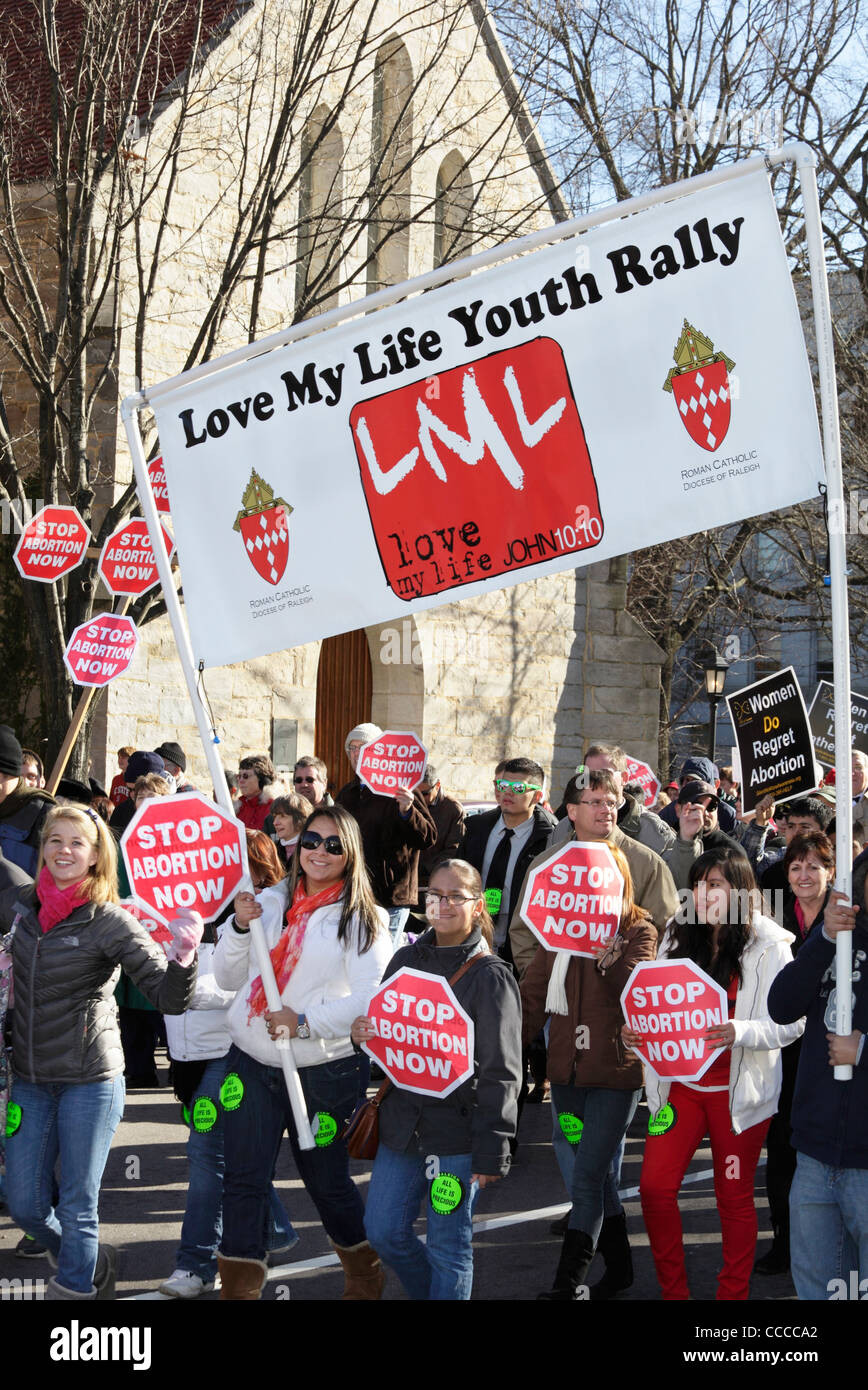 People carry signs that read 'Stop Abortion Now' during the annual March for Life in downtown Raleigh, North - Stock Image