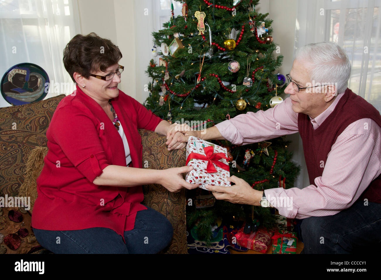 Senior man giving Christmas present to wife. 60-65 year old man ...
