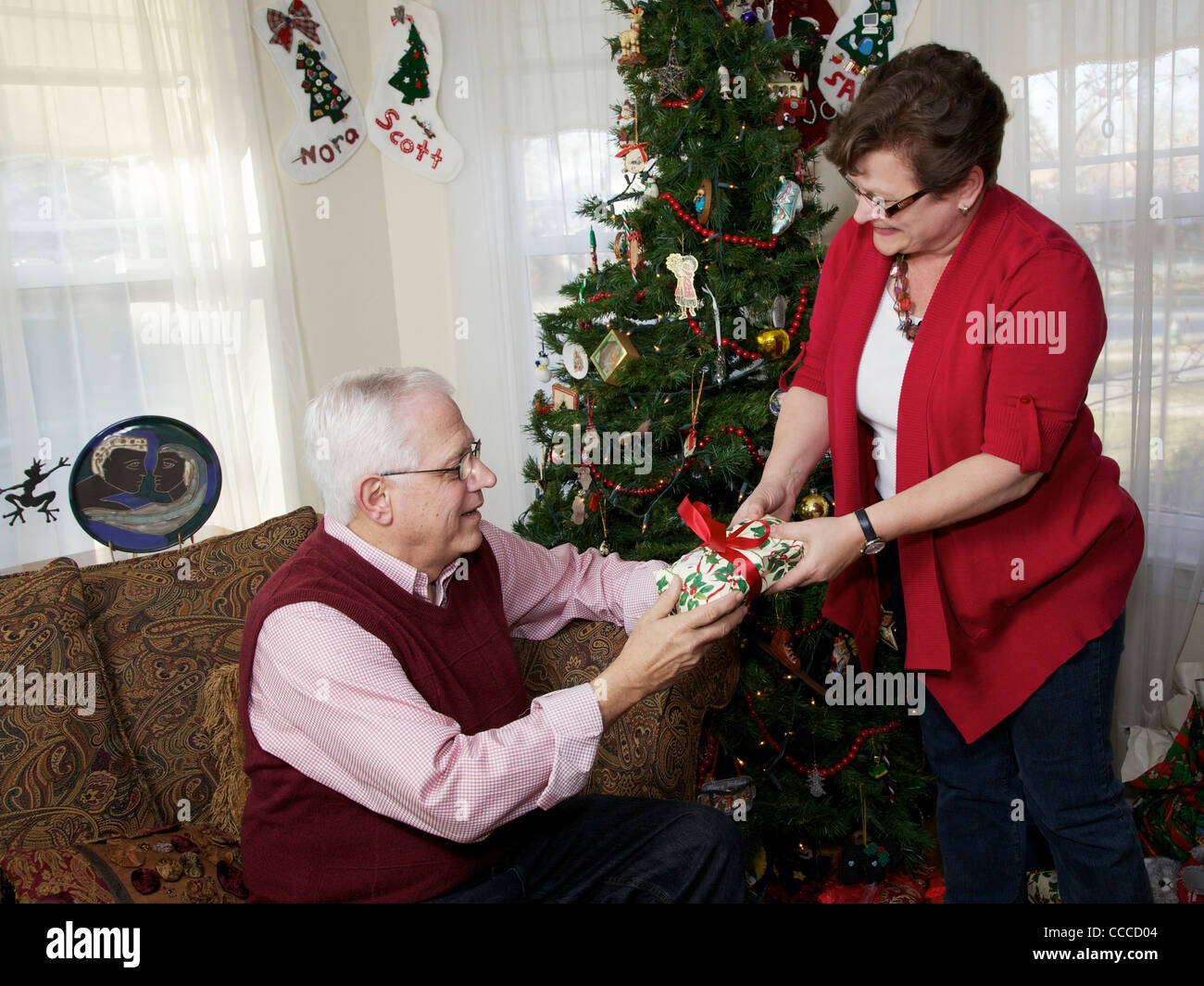 50-60 year old woman giving Christmas present to husband Stock Photo ...
