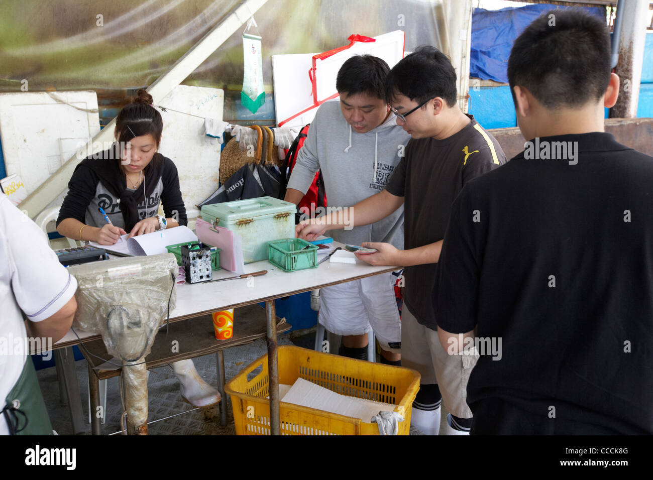 buyers and vendors settle up at the end of the selling day aberdeen wholesale fish and seafood market hong kong - Stock Image