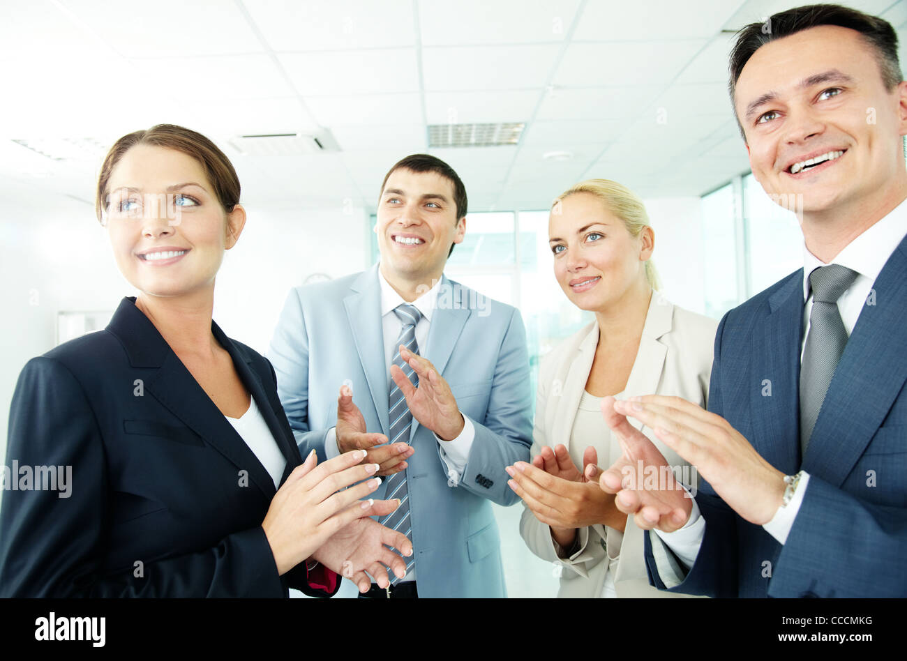 Photo of business partners applauding while looking at spokesman - Stock Image