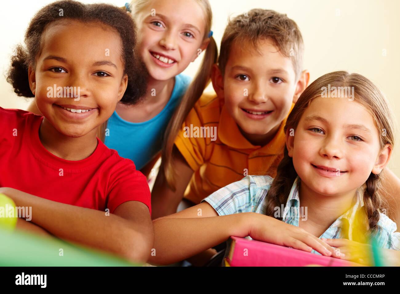 Portrait of smart schoolchildren looking at camera in classroom - Stock Image