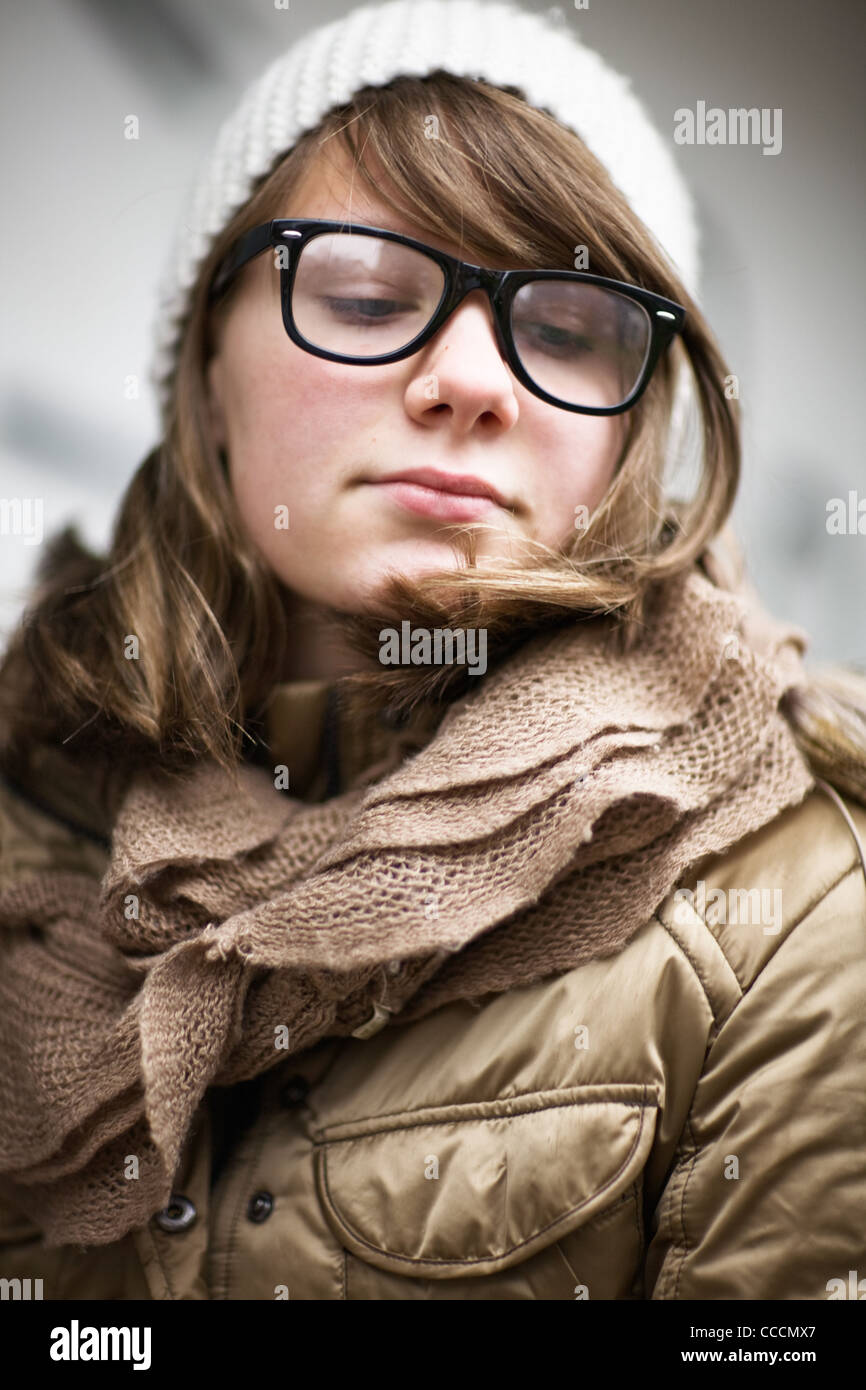 e9e7a8ff34b Teenage girl wearing fashionable eyeglasses with retro frames and white  knit hat