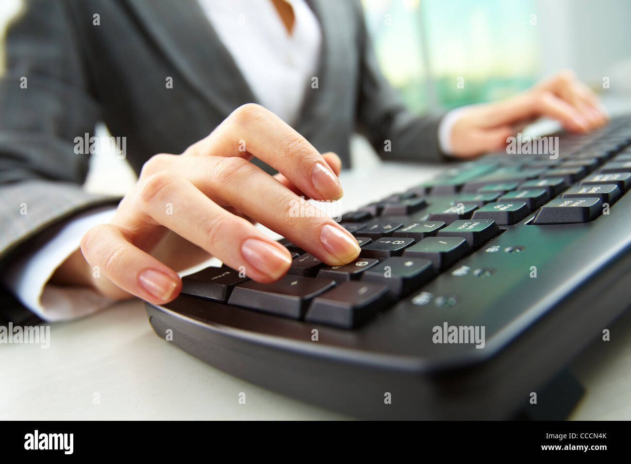 Macro image of human hand with forefinger going to press key on keyboard - Stock Image