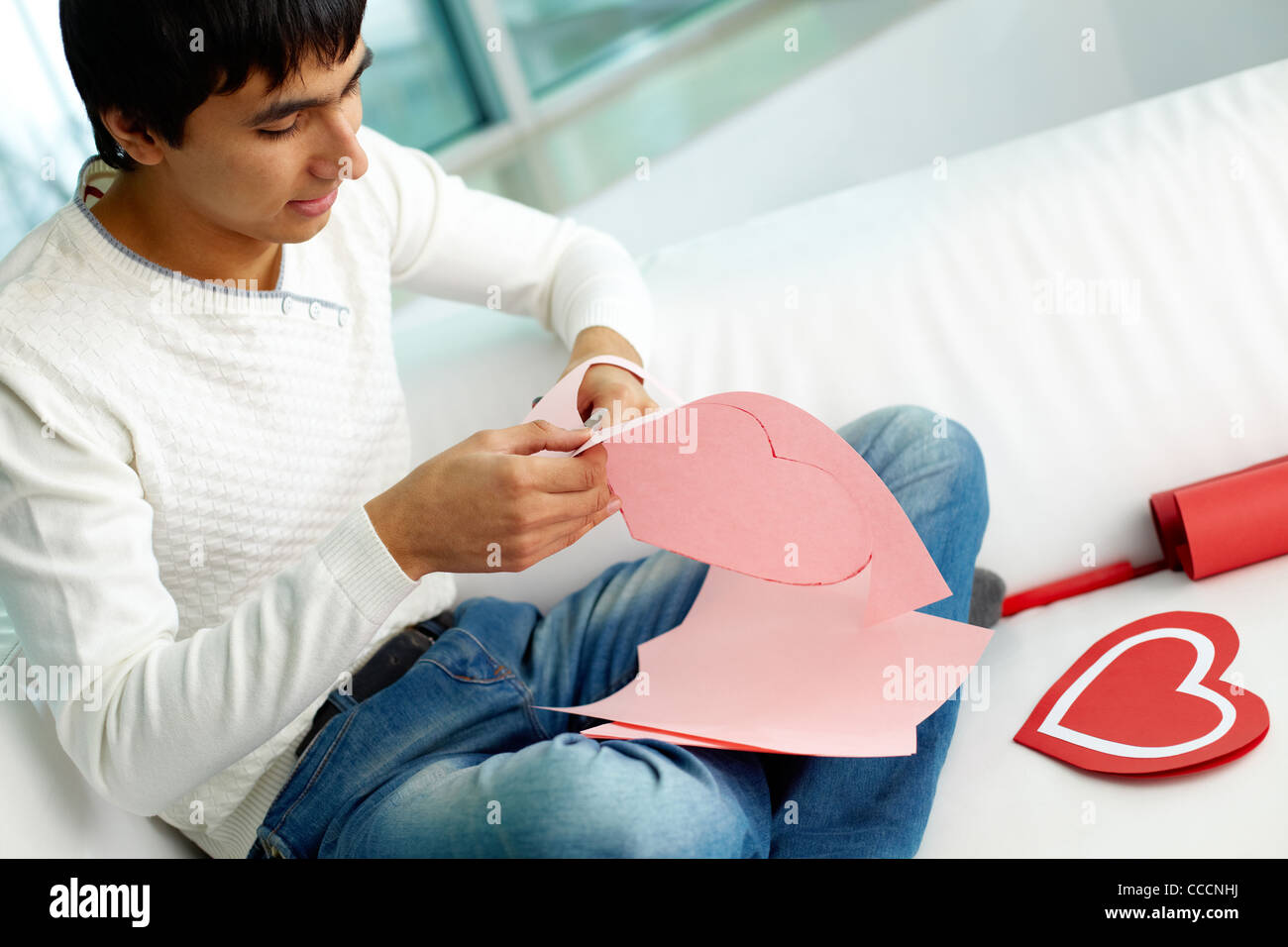 Image of handsome man cutting paper heart before St. Valentine day - Stock Image