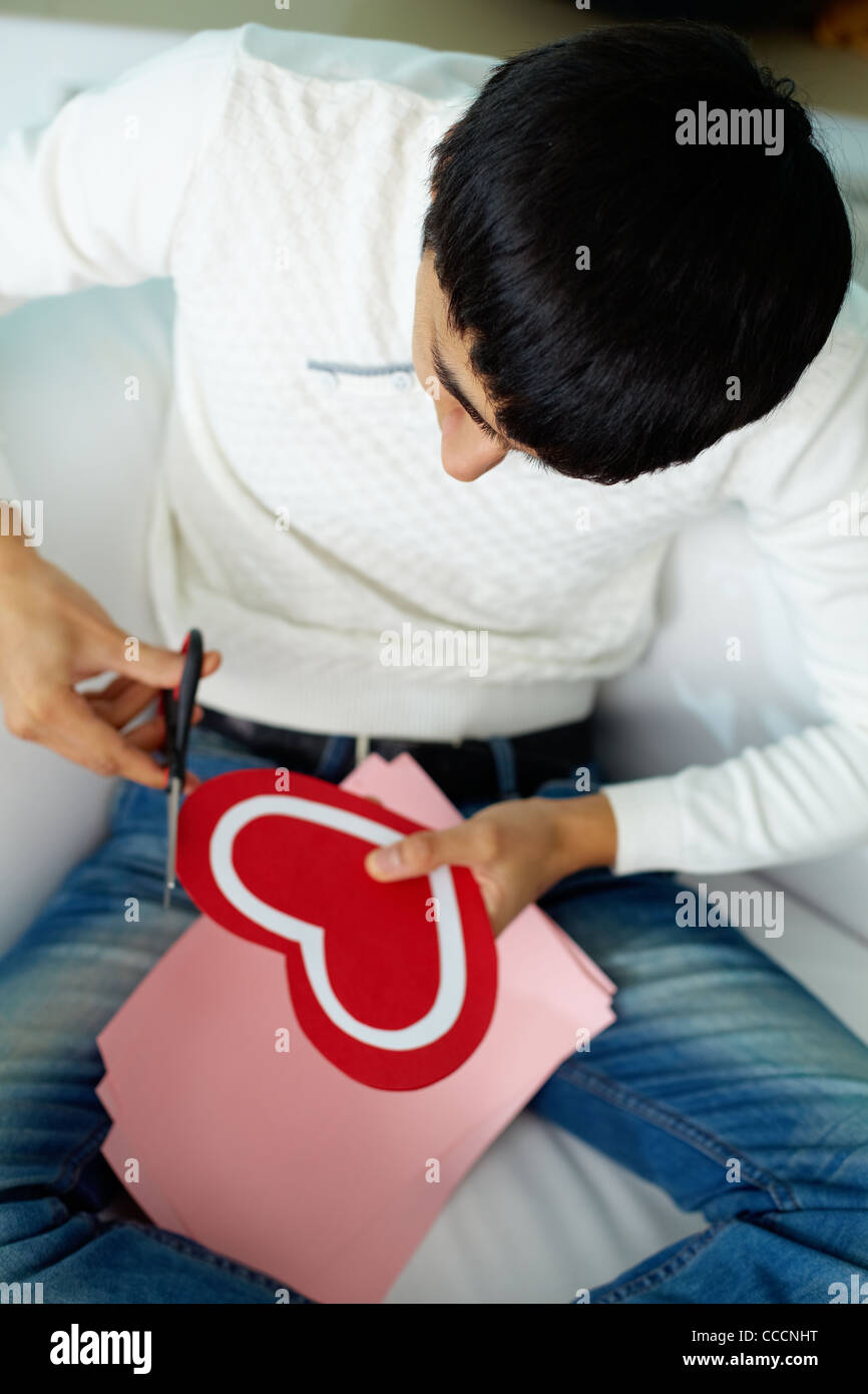 Above angle of handsome man cutting paper heart for St. Valentine day - Stock Image