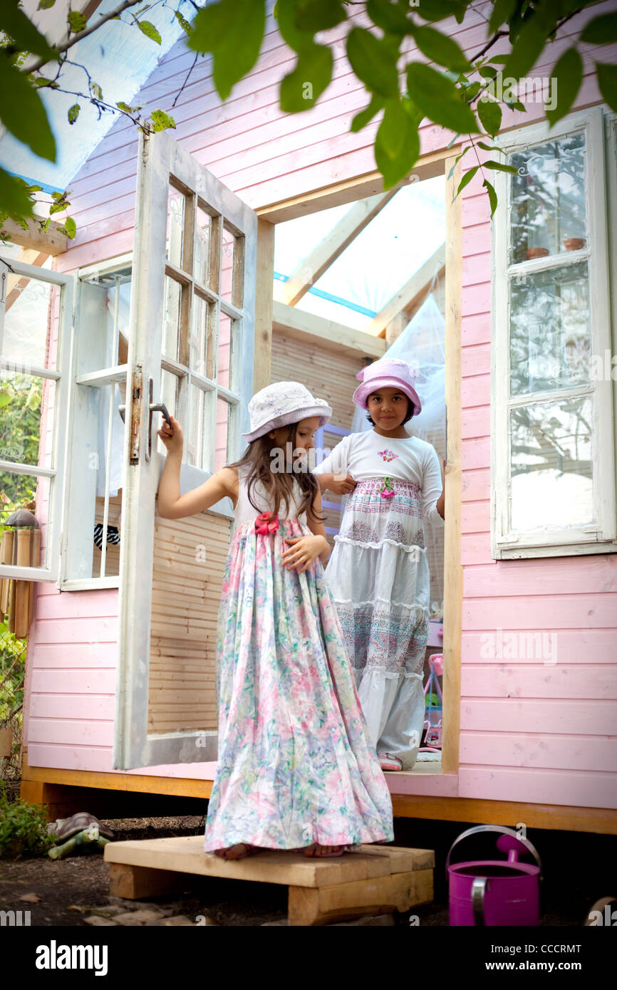 Sweet little girls  on the door of her doll house - Stock Image