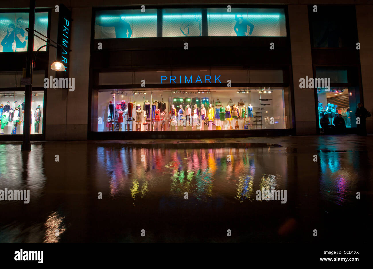 Primark shopfront and reflection in flood water after water mains burst along Oxford Street, London, UK. - Stock Image