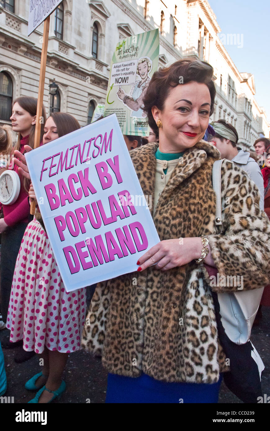 Placard 'Feminism, back by popular demand' held by smiling woman dressed in 1950s faux leopard clothes, - Stock Image