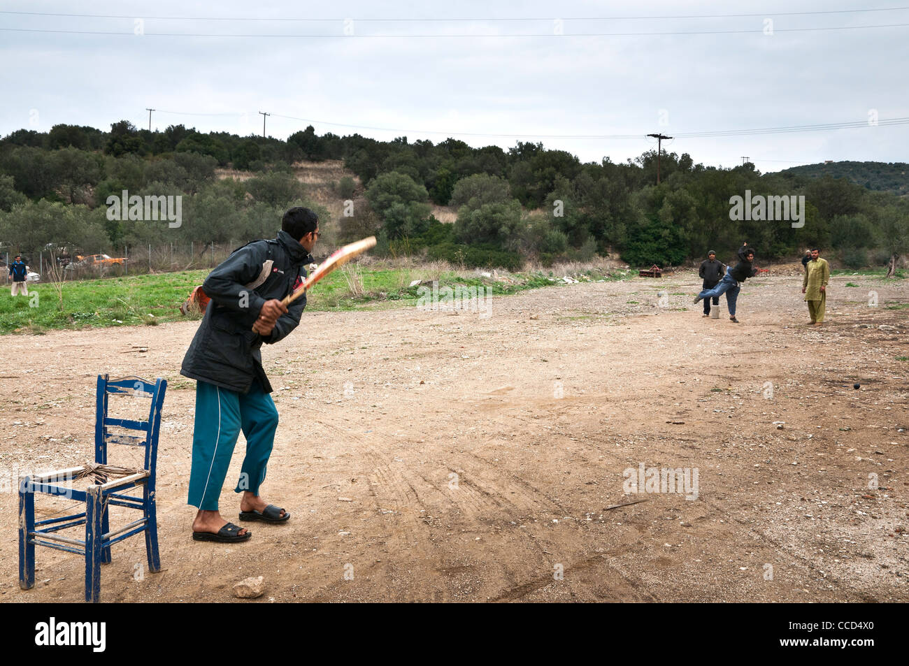 Pakistani, immigrant workers playing cricket in their lunch break, near Methana, Argolis, Peloponnese, Greece - Stock Image