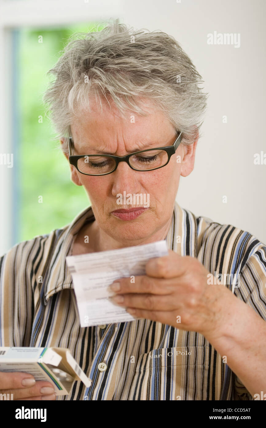 Older female person is reading an instruction leaflet Stock Photo