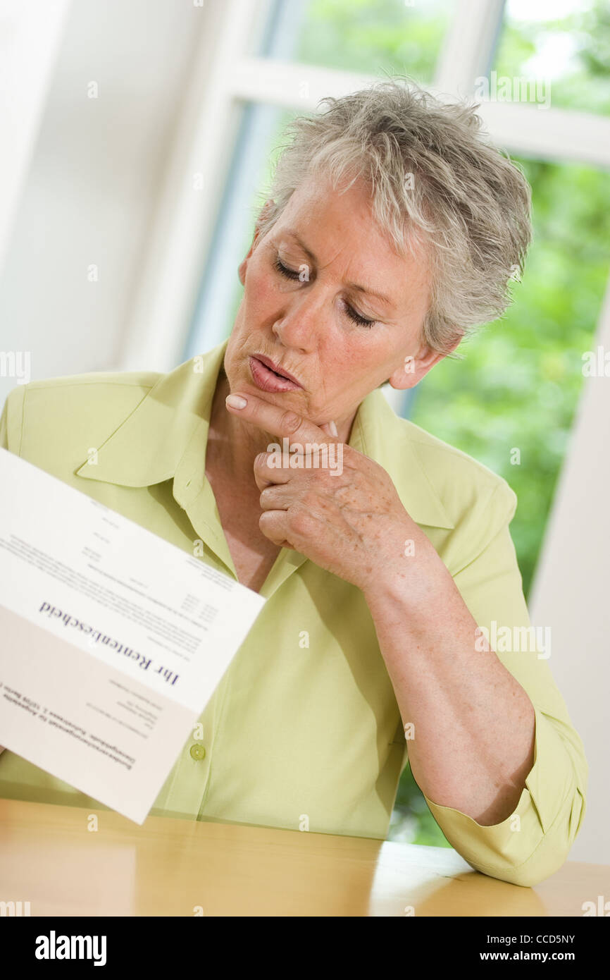Older female person looking at pension award - Stock Image