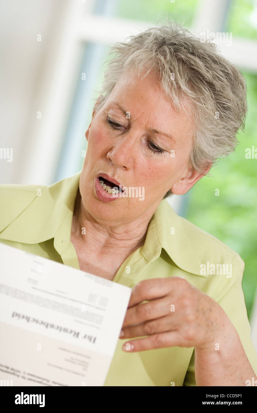 Older female person looking at pension award Stock Photo
