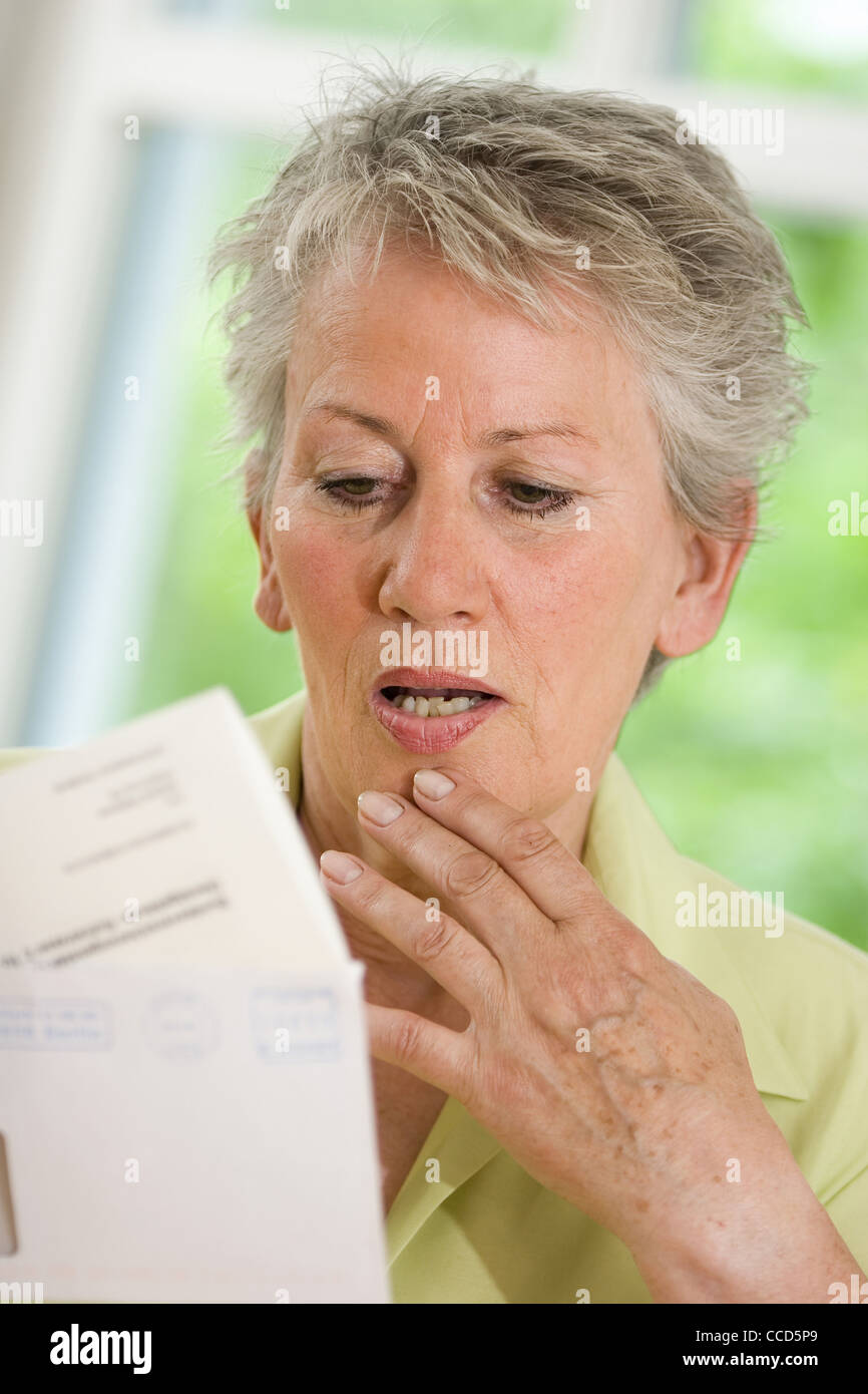 Older female person looking at official letter - Stock Image
