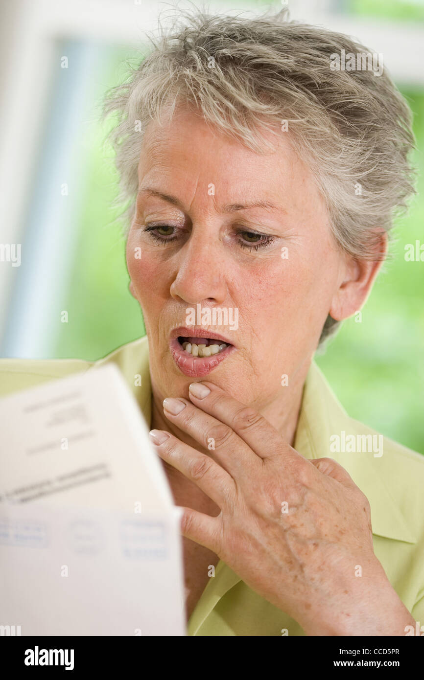 Older female person looking at official letter Stock Photo