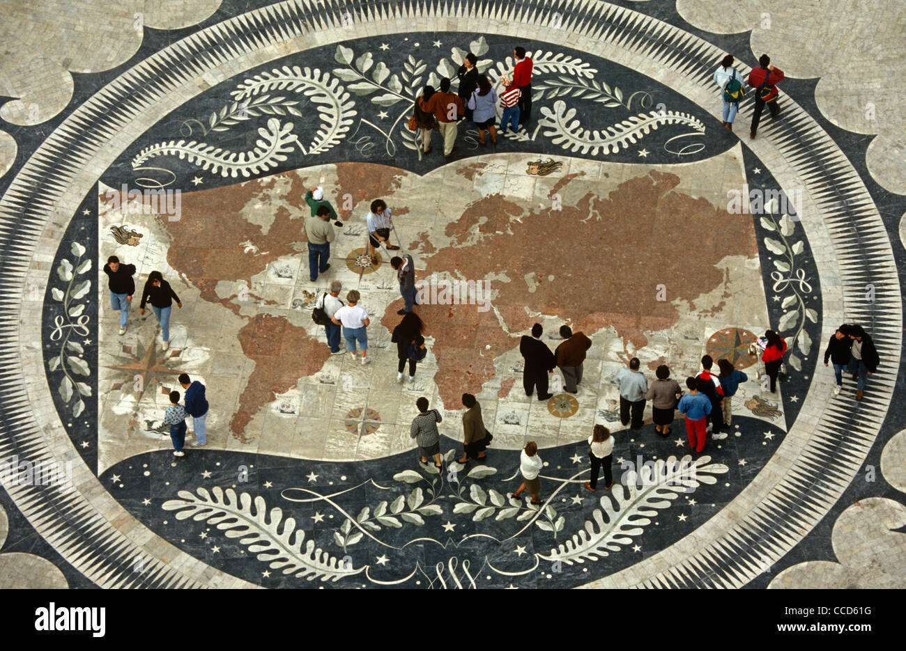 Portugese pedestrians walk over a world map on the pavement beneath the Monument of Discoveries, Lisbon. - Stock Image