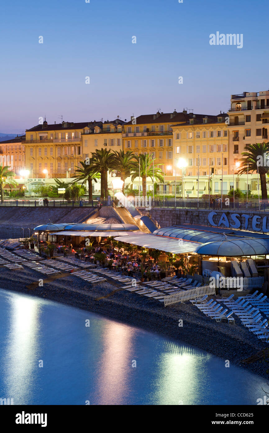 Night-time view of a restaurant on the Baie des Anges beach in Nice on the Mediterranean coast in southern France. - Stock Image