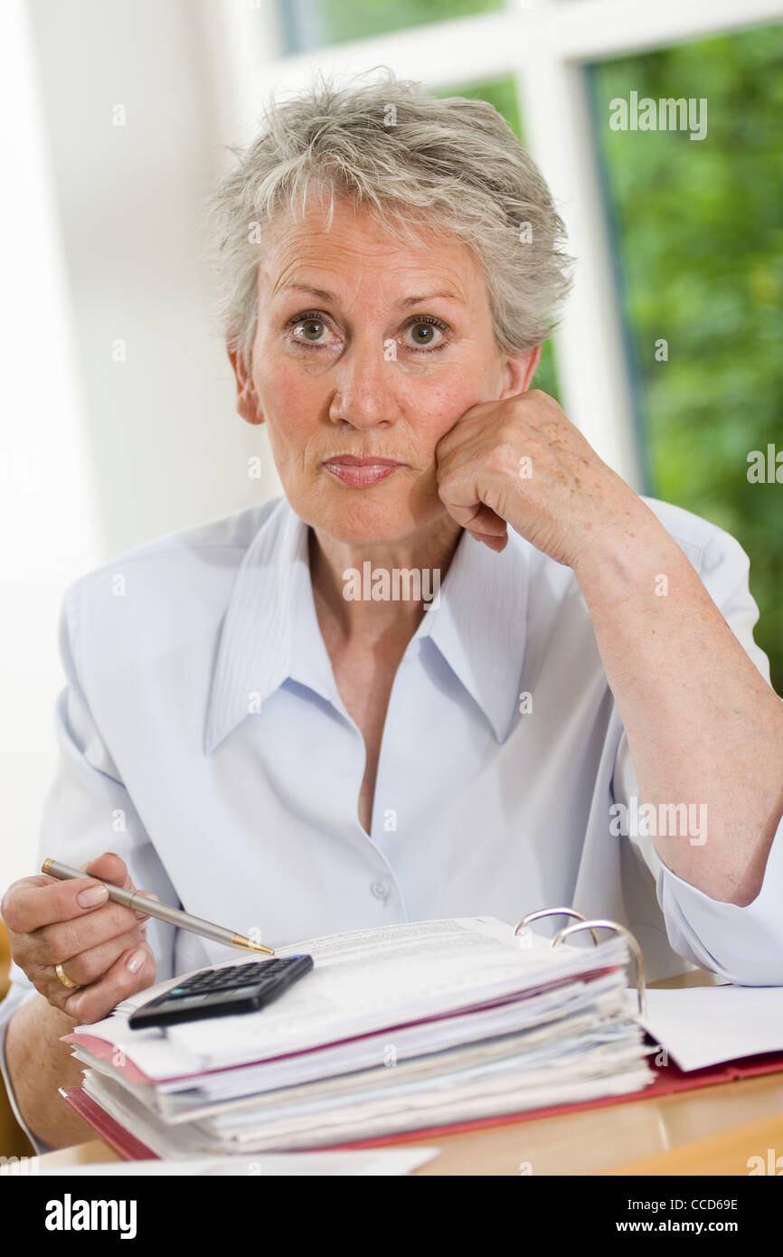 Older female person with a calculator Stock Photo