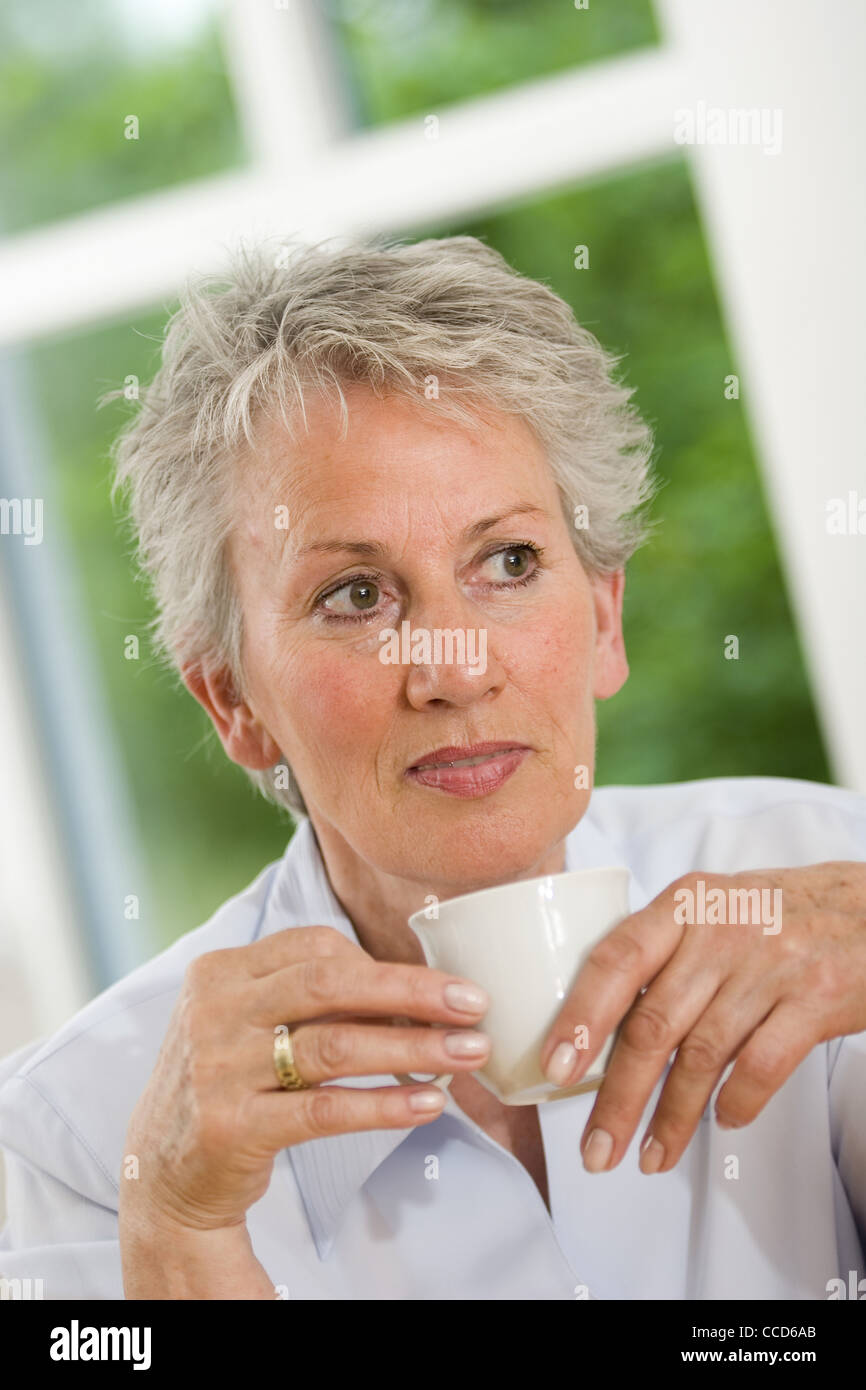 Older female person drinking coffee - Stock Image