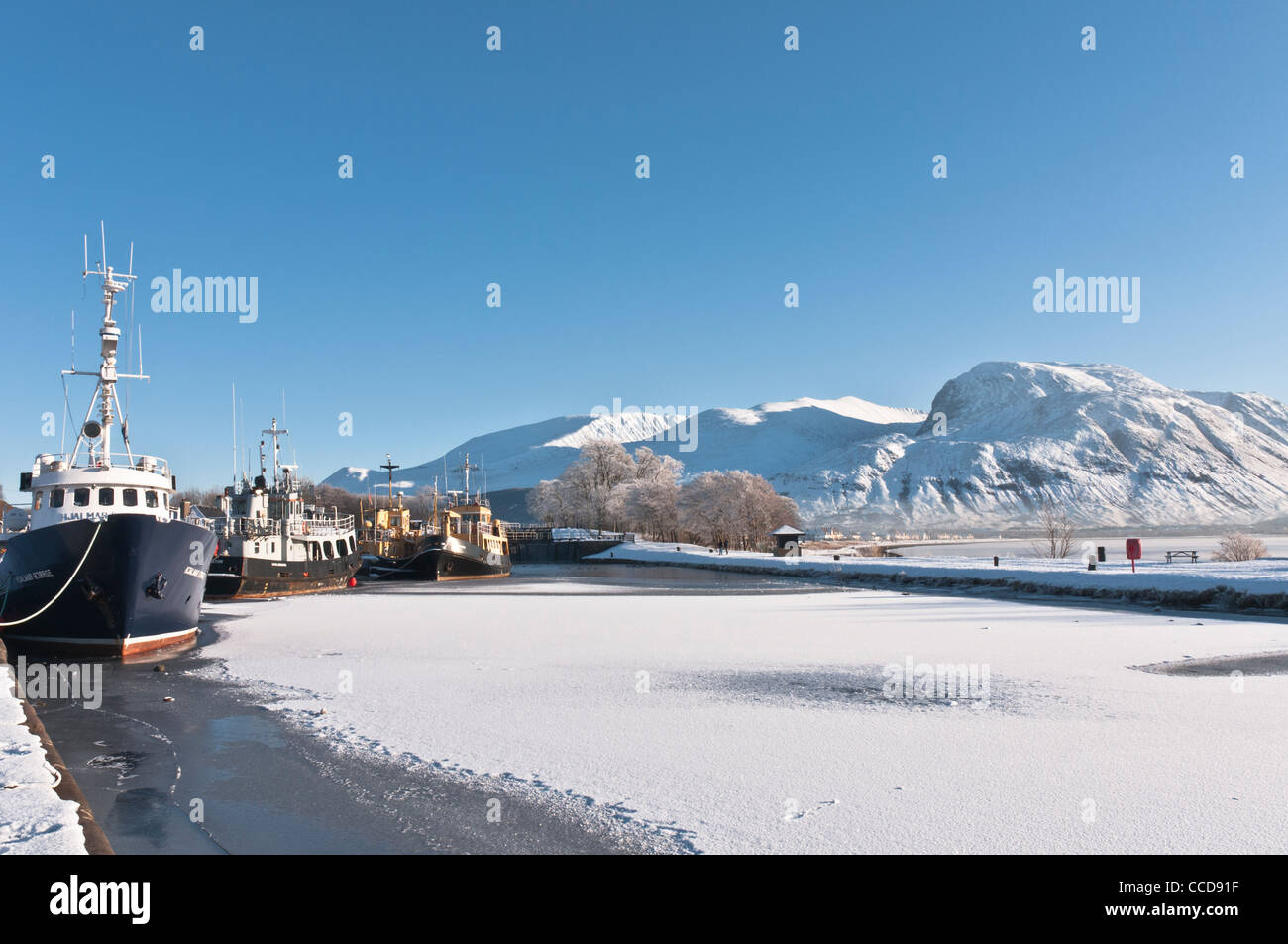 Boats in frozen Caledonian Canal at Corpach nr Fort William with Ben Nevis Highland Scotland - Stock Image