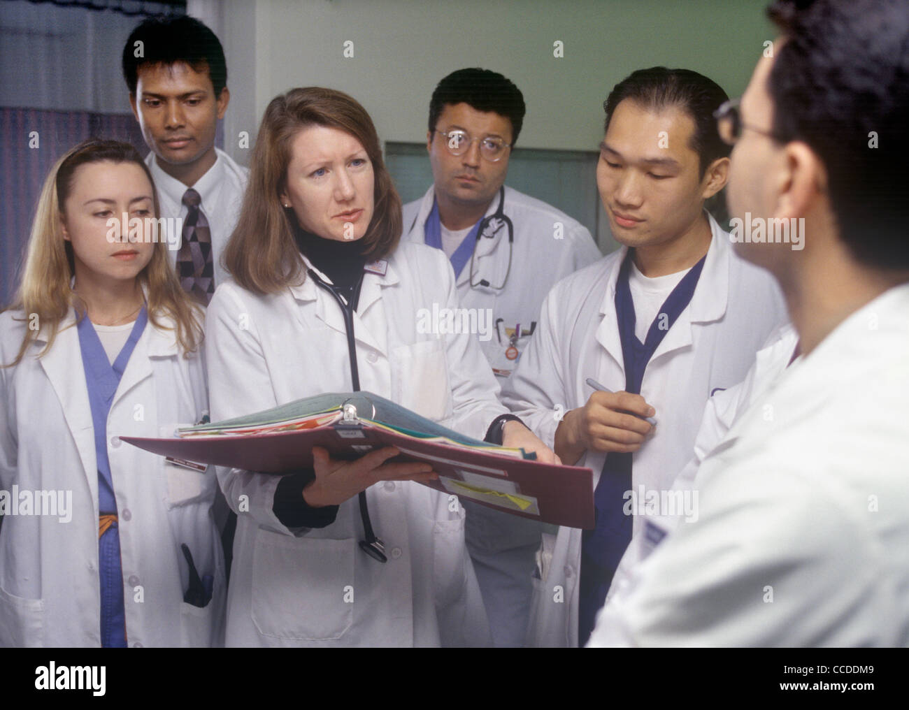 A physician discussing patient care with medical residents and holding a patient chart. - Stock Image