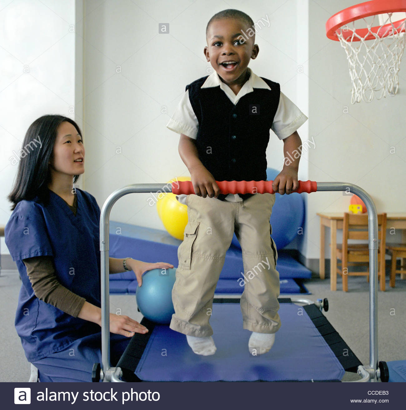 A young male child patient is helped by a physical therapist in the Rehabitation Department in a hospital. - Stock Image