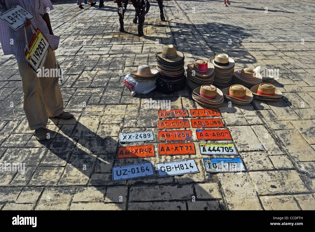 Street seller with car number plates and hats, Santo Domingo, Dominican Republic (Republica Dominicana), Caribbean, - Stock Image