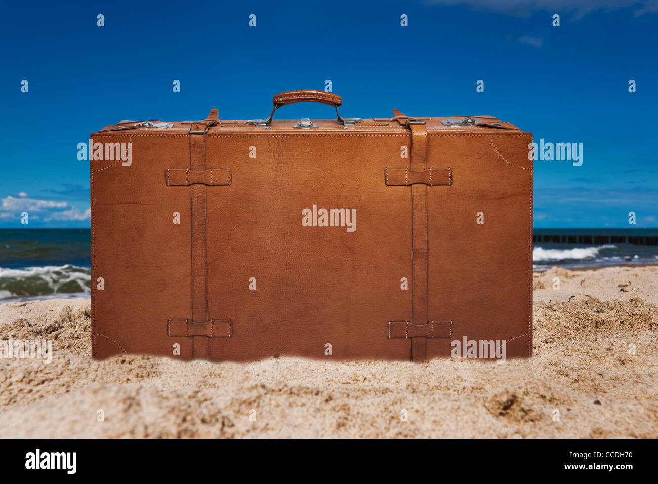 Ein alter brauner Lederkoffer steht am Sandstrand   a old brown leather suitcase upright at the sandy beach - Stock Image