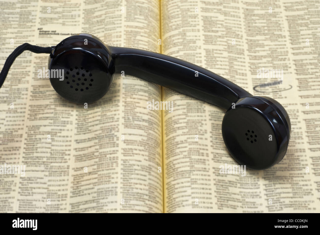 Detail photo of an old telephone receiver, lying on a phone book - Stock Image